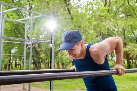 Attractive fitness man doing exercises in a summer park