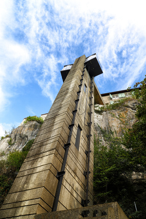Elevator outdoors near the stone cliff and blue sky with white clouds background