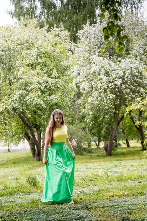 Beautiful young woman near blossoming apple tree