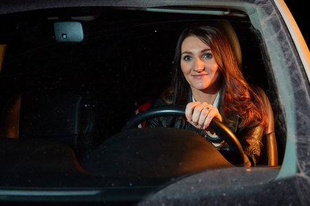 Fashionable young woman in a black leather jacket in a car in the black night and colour light behing her