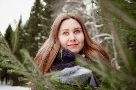 Portrait of a girl in a pine forest on a winter day. Single walk