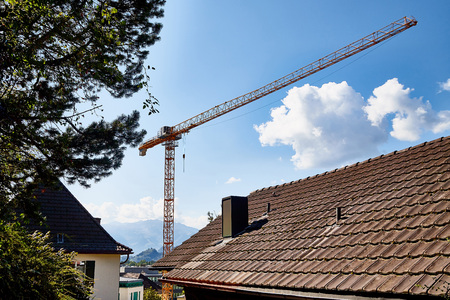 Tower crane and building against mountain and blue sky with white clouds
