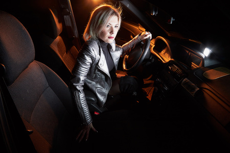 Fashionable young woman in a silver leather jacket in a car in the black night and colour light behing her Stock Photo