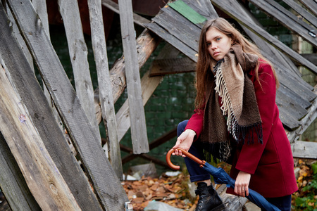 Girl with long hair in a red coat in an abandoned old building in late autumn