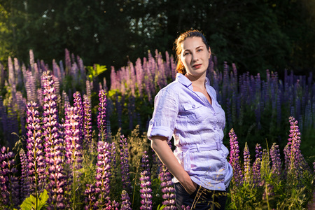 Nice woman in a field of purple lupines in a summer day Imagens - 124742138