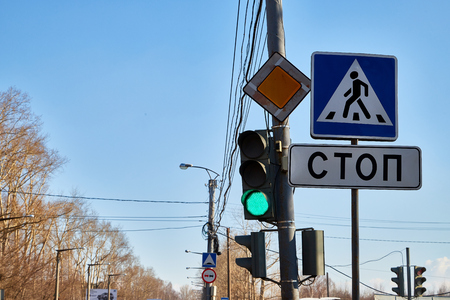 Traffic light with three colors and a sign with the inscription stop in Russian and blue sky with branch of tree in the background Banco de Imagens