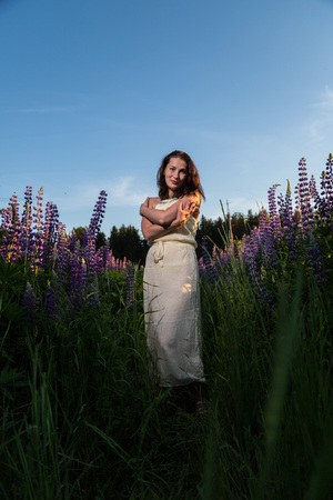 Nice woman in a field of purple lupines in a summer day Imagens - 124742011