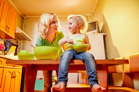 Mother and her three years old blonde daughter are cooking in a kitchen. Pampering with green plate on the table. Funny photoshoot of a little girl and an adult woman