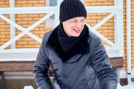 Portrait of an ordinary man in warm black clothes in a winter day. Russian man having fun outdoors