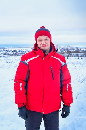 Portrait of an ordinary man in red warm clothes in a winter day. Snowboarder or skier outdoors and village on the horizon behind him Stock Photo
