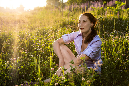 Nice woman in a field of purple lupines in a summer day