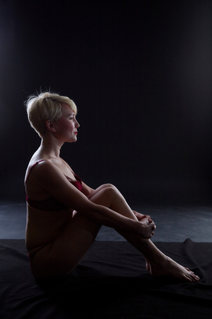 Sexy blonde girl during professional photo shoot in dark room. Model in a red lingerie and erotic underwear. Black background Banco de Imagens