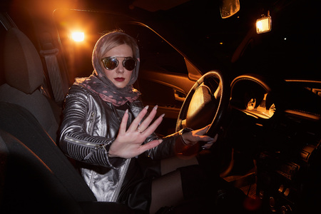 Fashionable young woman in a silver leather jacket in a car in the black night and colour light behing her Banco de Imagens