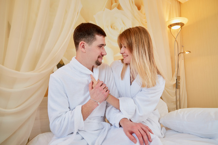Couple of tourists resting in beautiful hotel room on vacations. Honemoon travelers in white bathrobe in the wedding room Stok Fotoğraf