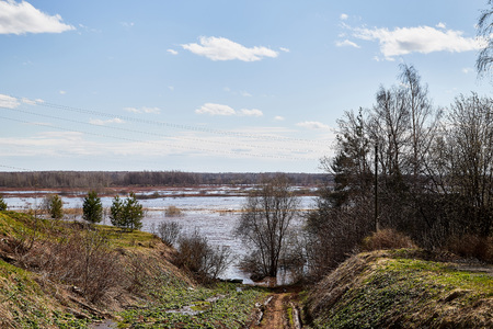 High water on a river or on a lake in sunny spring day. Russian nature landscape with water, trees and blue sky with white clouds 版權商用圖片 - 124716285
