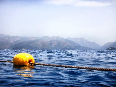 Sea surface with buoys and mountains in the distance. View and shooting from water in a summer day