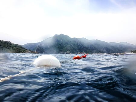 Sea surface with buoys and mountains in the distance. View and shooting from water in a summer day 版權商用圖片 - 124716003