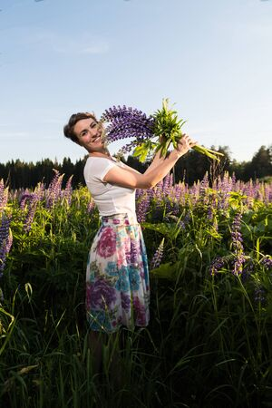 Beautiful girl in a field of purple lupines in a summer day Imagens - 124715936