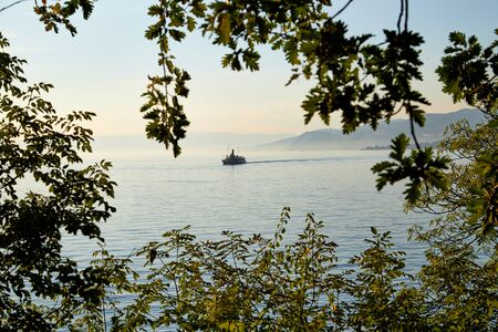 View on lake with ship through branch of tree during sunset in summer evening 版權商用圖片 - 124715836