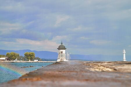 Lighthouse on the pier in a nice day with blue sky and clouds in summer day Фото со стока