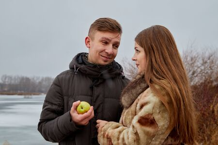 Romantic couple in love on autumn or winter walk near lake. The guy treats the girl with an Apple 版權商用圖片 - 124715820