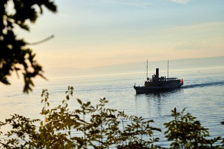 View on lake with ship through branch of tree during sunset in summer evening