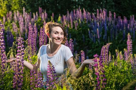 Beautiful girl in a field of purple lupines in a summer day Stock Photo - 124715793