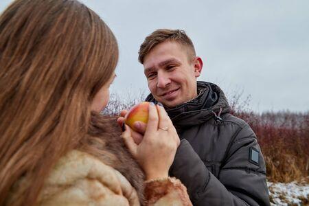 Romantic couple in love on autumn or winter walk near lake. The guy treats the girl with an Apple 版權商用圖片 - 124715797