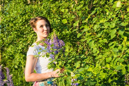 Portrait of a beautiful girl with lupines in a summer day Imagens