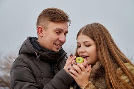 Romantic couple in love on autumn or winter walk near lake. The guy treats the girl with an Apple 版權商用圖片