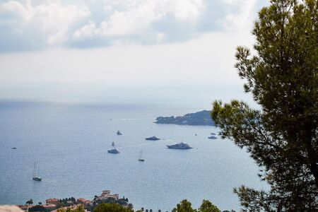 View from a high cliff to landscape with greenery to the sea, blue sky, white clouds and ships on a Sunny day Фото со стока