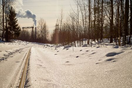 Winter railway rails in the snow. Rails go into the distance in a cold sunny day