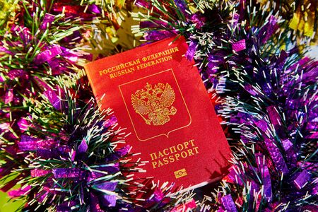 Colorful Christmas tinsel lined with rows and passport of of citizen of Russia. The concept of traveling abroad in the New year Stock Photo