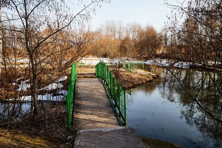 Green Bridge over small river in a nice sunny day in early spring. Russian nature landscape with water, trees and blue sky