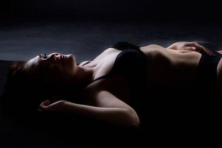 Sexy Mädchen beim professionellen Fotoshooting in der Dunkelkammer. Modell in einer schwarzen Wäsche und Unterwäsche. Schwarzer Hintergrund