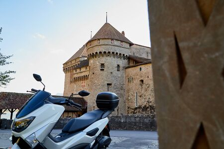 Modern motorcycle in the courtyard of an ancient stone castle. Summer travel concept