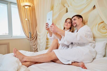 Couple of tourists resting in beautiful hotel room on vacations. Honemoon travelers in white bathrobe in the wedding room. Boy and a girl doing a selfie for tablet Stock Photo