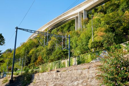 Railway at the foot of the mountain separated by a wall surrounded by greenery on a summer day. Rail road near the town of Montreux at Lake Geneva in Switzerland Standard-Bild