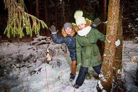 Children boy and girl walking in snow forest in a winter day. Teenagers having trip and rest in weekend outdoor. People in a warm dress in a cold day Imagens