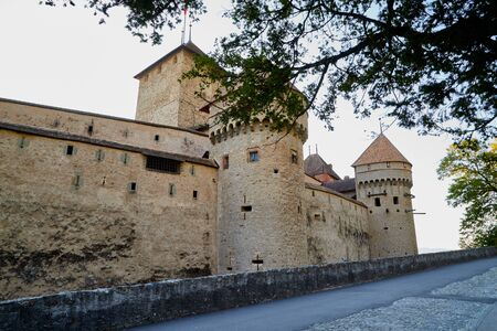 Walls and towers of a castle through the branches of trees at sunset. Beautiful castle in Europe in evening