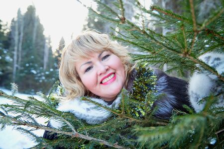 Portrait of beautiful plump woman in a nice winter forest full of snow. Lady in fur coat and fluffy gloves