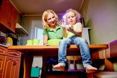 Mother and her three years old blonde daughter are cooking in a kitchen. Pampering with flour and dough on the table. Funny photoshoot of a little girl and an adult woman