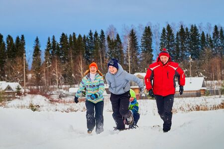 Portrait of a family with four people having fun in the snow. Dad, mom and two sons in winter day outdoor