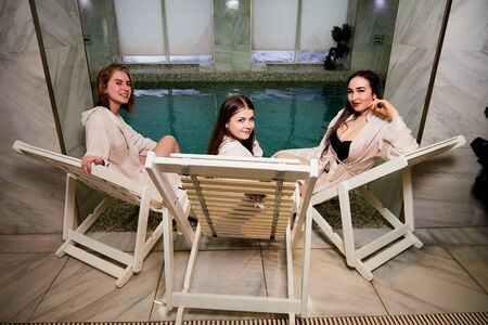 Three cute girls in bath robes on wooden chairs in the indoor pool. Female friends on vacation at the Spa on the sun bed