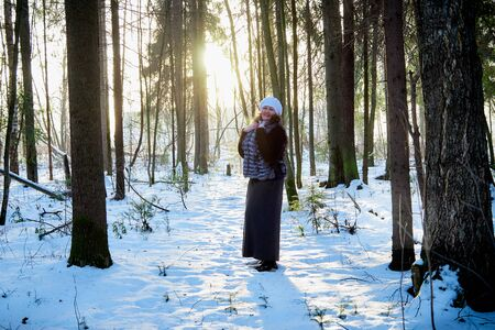 Plump woman in a nice winter forest full of snow. Lady in fur coat Imagens
