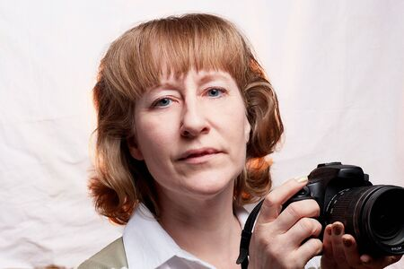Blonde-haired female photographer with camera in her hands on a white background. Woman taking a photo Imagens