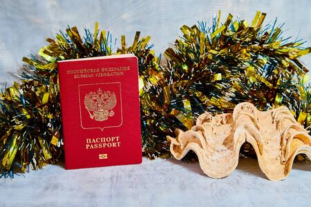 Colorful Christmas tinsel, passport citizen of Russia and big shell. The concept of traveling abroad in the New year Imagens