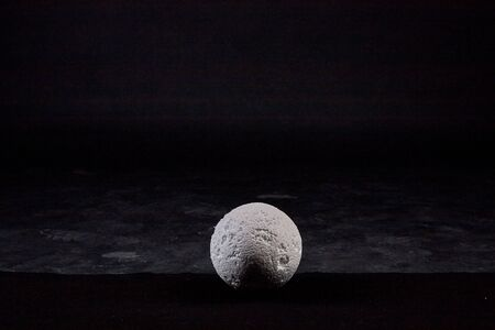 White ball of foam on a black background in the Studio and empty arround