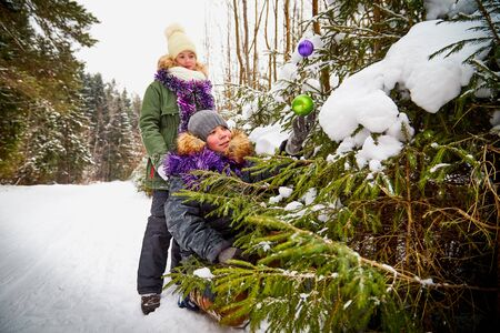 Children decorating a Christmas tree in snow forest in a winter day. Teenagers having rest and fun in weekend outdoor. People in a warm dress and in tinsel in a cold day