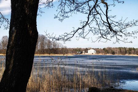 Landscape with lake covered with ice and trees around with Sunny spring or autumn day Imagens